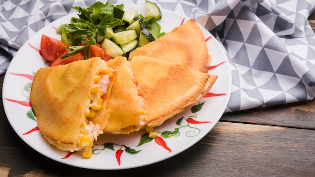 Delicioso bolo perto de salada de legumes no prato Foto gratuita