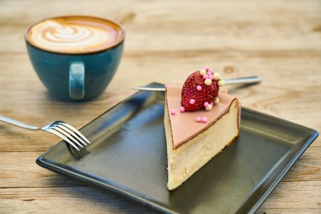 Delicioso café com leite e cheesecake na mesa de madeira Foto Premium