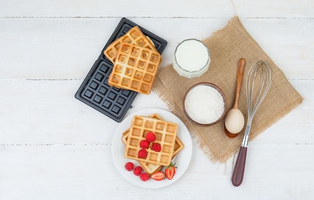 Delicioso café da manhã com waffles, leite e frutas vermelhas Foto gratuita