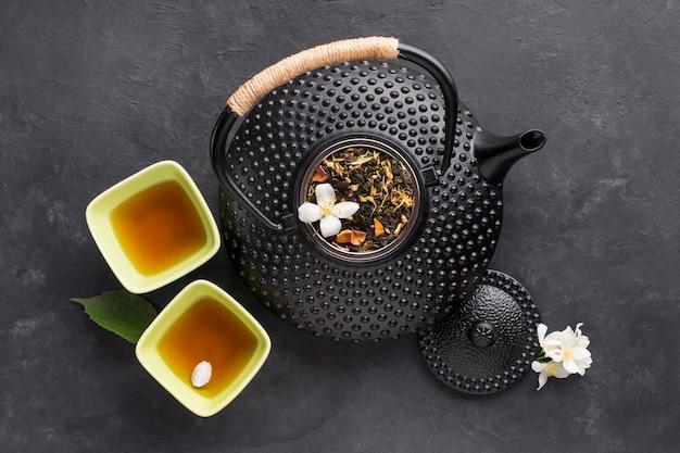 Delicioso chá de ervas saudável em tigela com bule preto no plano de fundo texturizado Foto gratuita