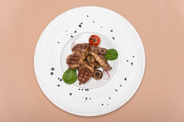 Delicioso costelas de cordeiro grelhado, com tomate grill e decorado com rabanete, espinafre, folha verde Foto Premium
