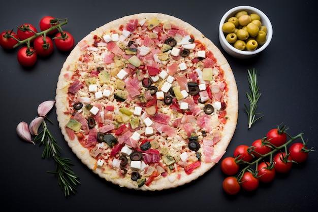 Delicioso enfeite de pizza com vários ingredientes Foto gratuita