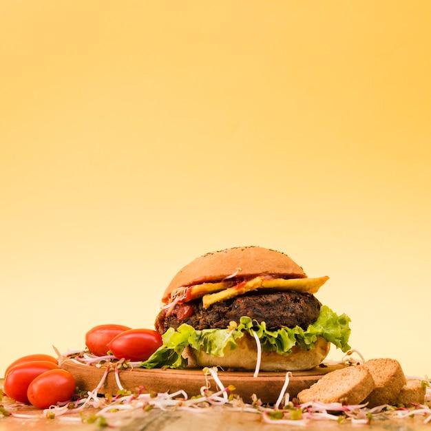 Delicioso hambúrguer com tomate cereja; brotos e fatias de pão na tábua de cortar contra um fundo amarelo Foto gratuita