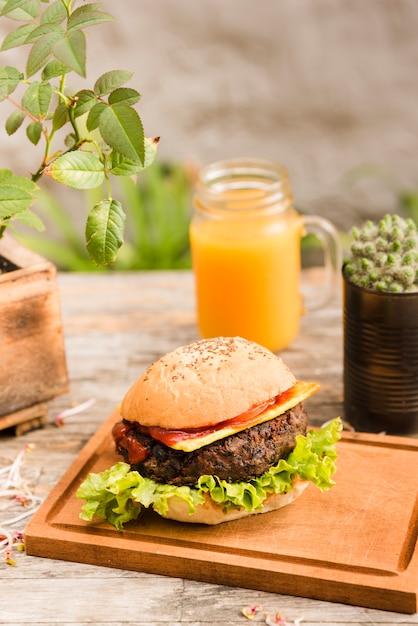 Delicioso hambúrguer na tábua de cortar servido com jarra de suco na mesa de madeira Foto gratuita