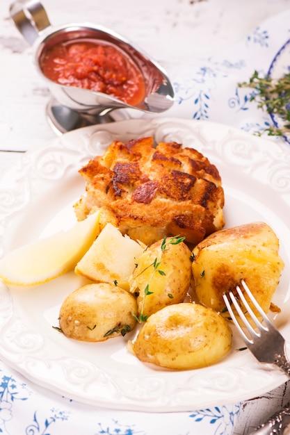 Delicioso jantar: batatas assadas com tomilho e costeletas Foto Premium