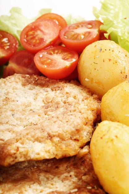 Delicioso jantar com bifes, batatas cozidas e salada Foto gratuita