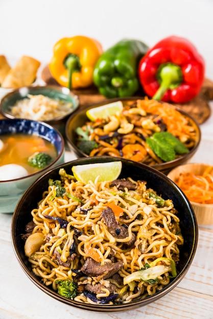Delicioso macarrão e sopa com pimentão na mesa Foto gratuita