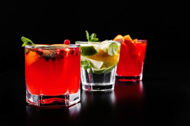 Delicioso mojito, rum e coca-cola, laranja-sangue e coquetéis de vodka servidos com frutas Foto gratuita
