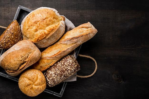 Delicioso pão branco e integral na cesta de madeira Foto Premium