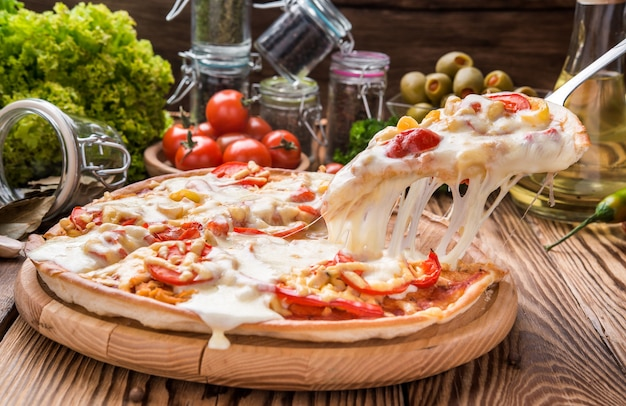 Delicioso pedaço de pizza quente na bandeja de madeira com queijo derretido Foto Premium