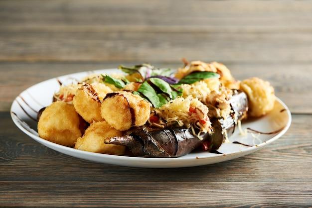 Delicioso prato quente de restaurante, inclui batata dourada frita com queijo e suculentos vegetais grelhados. saboroso aperitivo decorado com folhas de hortelã fresca e molho. Foto gratuita