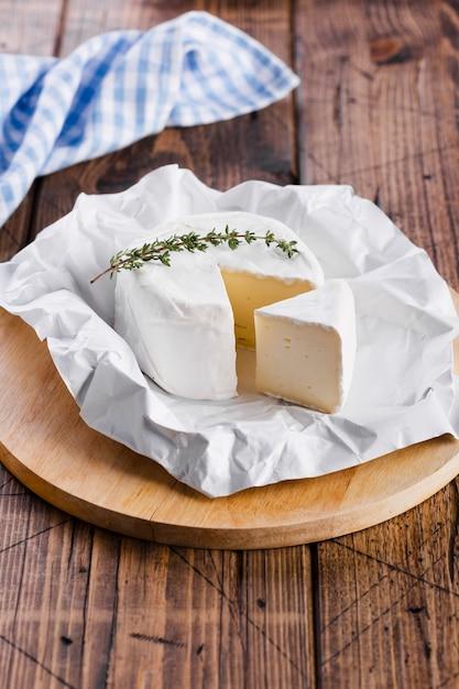 Delicioso queijo fatiado na placa de corte vista alta Foto gratuita
