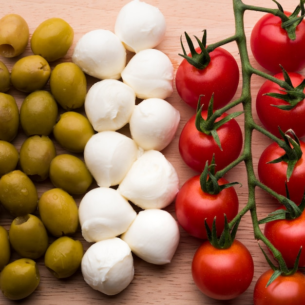Delicioso queijo mussarela; frescos tomates vermelhos e azeitonas molhadas na mesa de madeira Foto gratuita