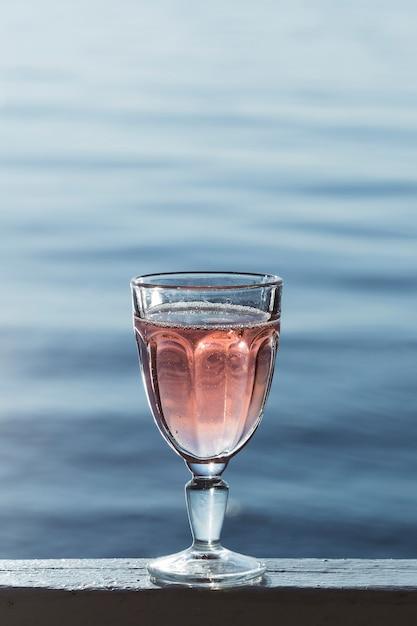 Delicioso vinho rosé em um copo ao lado do mar Foto Premium