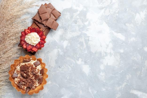 Deliciosos bolos cremosos com barras de chocolate na mesa branca bolo biscoito doce açúcar Foto gratuita