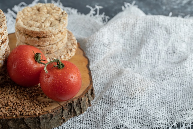 Deliciosos bolos de arroz, tomates e trigo sarraceno cru na peça de madeira Foto gratuita