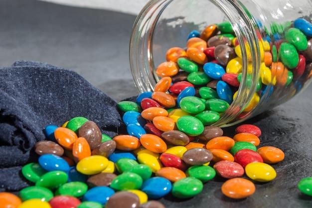 Deliciosos bombons de chocolate coloridos em frasco de vidro derramado Foto Premium