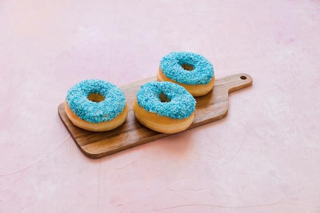 Deliciosos donuts azuis na tábua de madeira Foto gratuita
