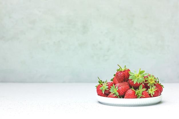 Deliciosos morangos orgânicos suculentos vermelhos maduros frescos em uma tigela branca Foto Premium