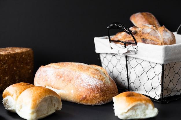 Deliciosos tipos de pão e cesta Foto gratuita