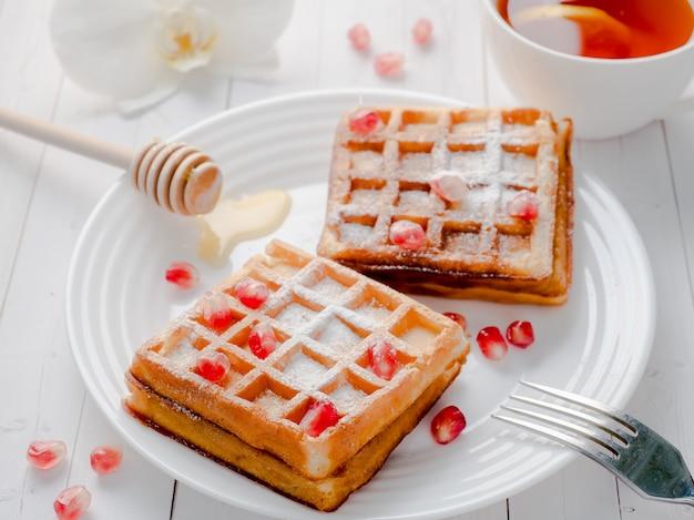 Deliciosos waffles de dar água na boca com sementes de mel e romã em um prato branco Foto Premium