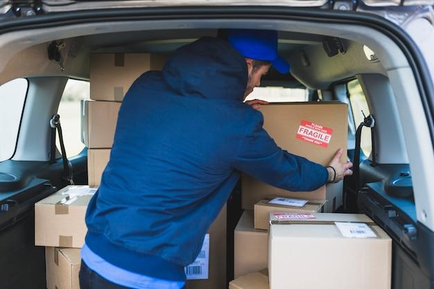 Deliveryman em carro com caixas de cartão Foto gratuita
