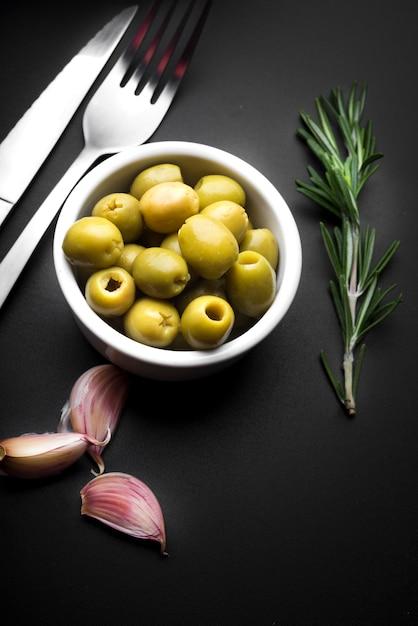 Dente de alho; tigela de azeitonas e alecrim com talheres na bancada da cozinha Foto gratuita