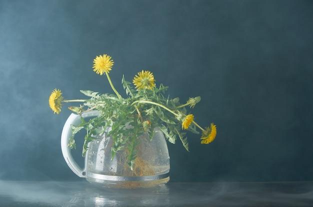 Dente de leão com raízes e folhas em um bule de vidro Foto Premium