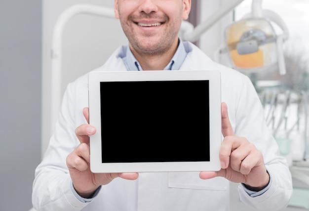 Dentista apresentando tablet Foto gratuita