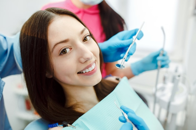 Dentista assistente e o paciente na clínica. Foto gratuita