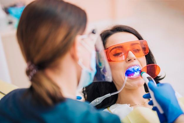 Dentista, clareamento, dentes, de, paciente, com, ultravioleta Foto gratuita