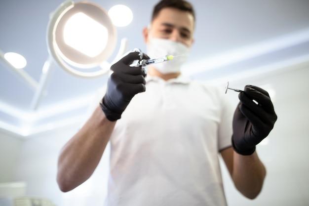 Dentista desfocado com instrumentos de odontologia Foto gratuita
