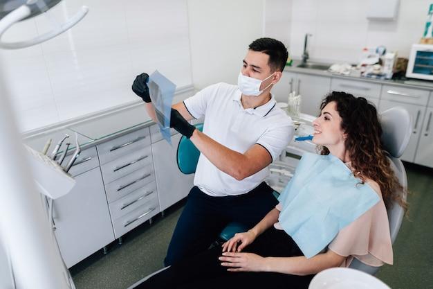 Dentista e paciente olhando para radiografia Foto gratuita