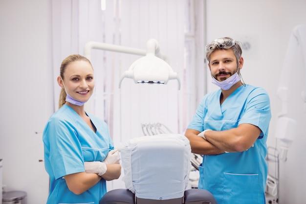 Dentista em pé com os braços cruzados na clínica odontológica Foto gratuita