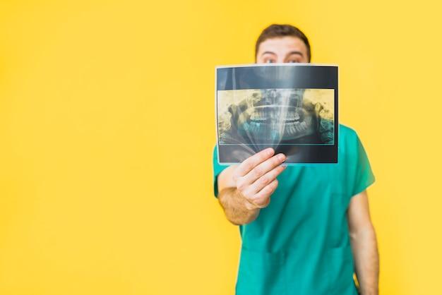 Dentista, em, uniforme, mostrando, dentes, raio x Foto gratuita