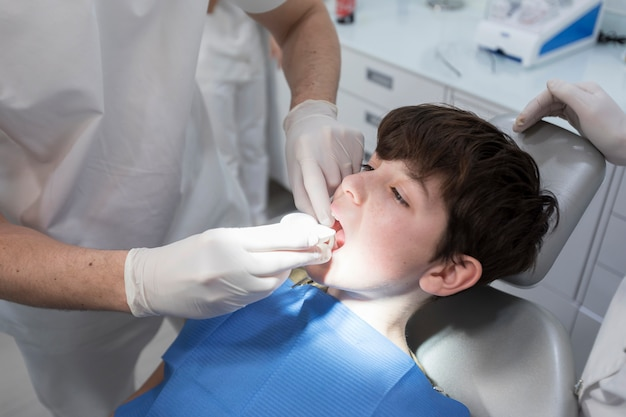 Dentista examinando os dentes do menino na clínica Foto Premium