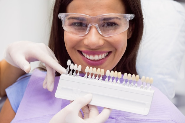 Dentista examinar paciente do sexo feminino com tons de dentes Foto gratuita