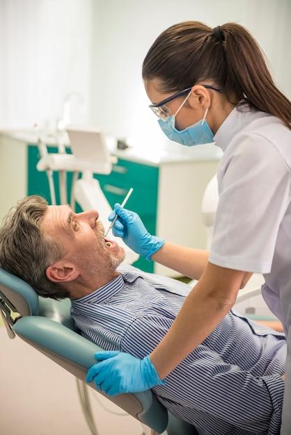 Dentista fêmea com seu cliente sênior que examina um paciente. Foto Premium