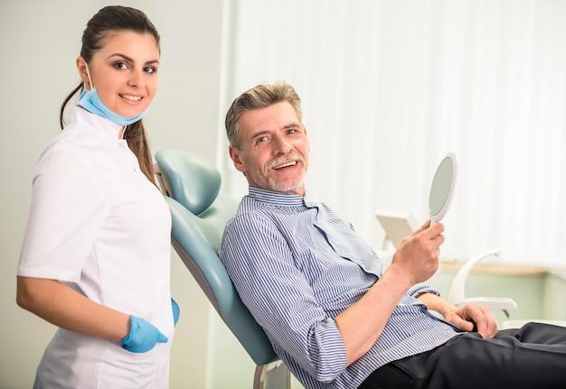 Dentista feminina com seu cliente sênior na clínica odontológica. Foto Premium