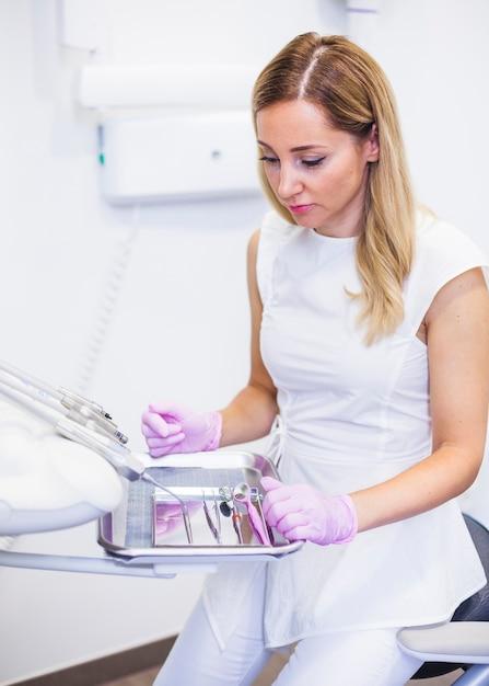 Dentista feminina olhando instrumentos odontológicos na bandeja Foto gratuita