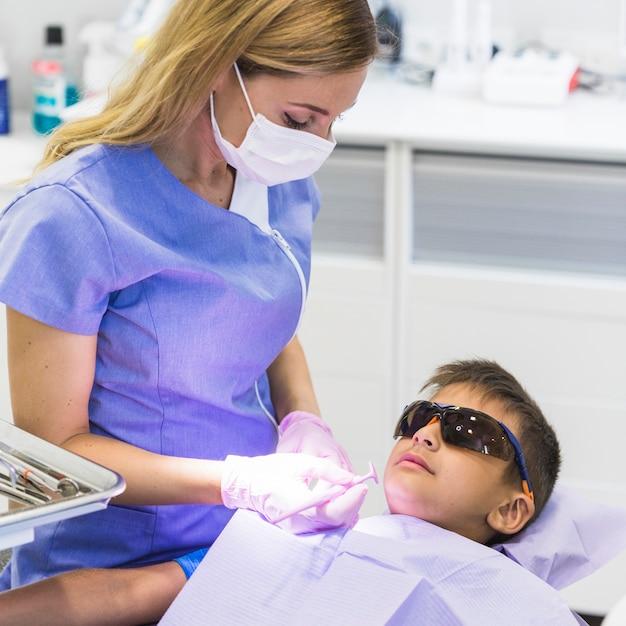 Dentista feminina, verificando os dentes do menino com espelho dental Foto gratuita