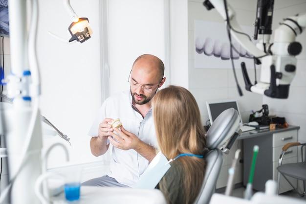 Dentista, mostrando, mandíbula dental, para, seu, femininas, paciente Foto gratuita