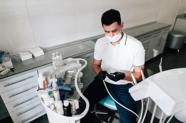 Dentista no escritório preparando instrumentos cirúrgicos Foto gratuita