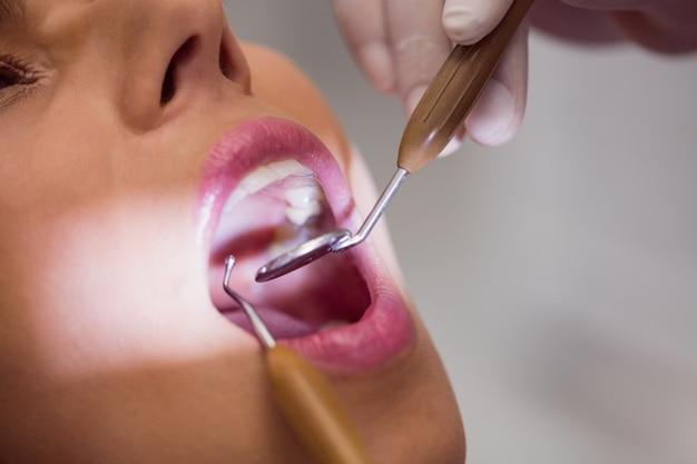 Dentista que examina os dentes pacientes do sexo feminino Foto gratuita