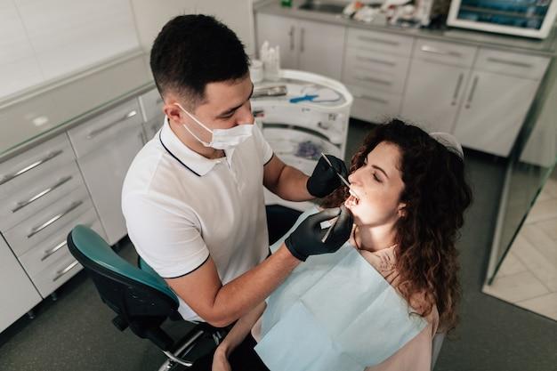 Dentista, realizando um check-up do paciente no escritório Foto gratuita