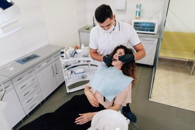 Dentista, realizando um check-up na mulher Foto gratuita
