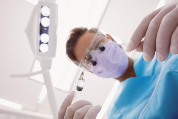 Dentista segurando ferramentas dentárias Foto gratuita