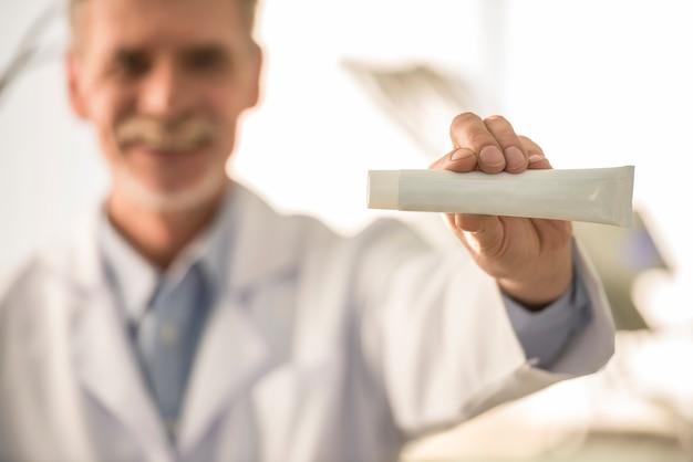 Dentista sênior, segurando, pasta de dentes Foto Premium