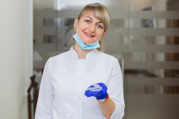 Dentista, sorrindo e segurando retentores invisíveis Foto gratuita