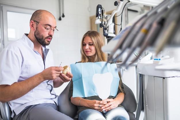 Dentista, trabalhando, ligado, dental, mandíbula, perto, femininas, paciente, sentando, ligado, cadeira dental Foto gratuita